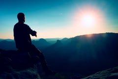 Turist- ta en vila stiligt sammanträde för den unga mannen på vagga och tycka omsikten in i dimmiga steniga berg royaltyfria foton