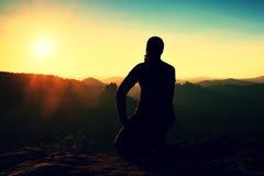 Turist- ta en vila stiligt sammanträde för den unga mannen på vagga och tycka omsikten in i dimmiga steniga berg royaltyfri bild