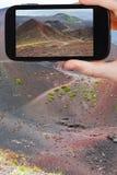 Turist- tagande foto av banan på lutning av krater Royaltyfri Bild