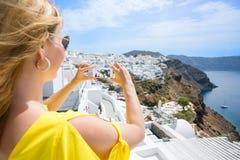 Turist- tagande foto av Santorini med mobiltelefonen royaltyfria bilder