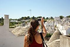 Turist- tagande loppbild med den mirrorless kameran av Alberobello trullicityscape under sommarferier Oigenkännlig kvinnlig Arkivbilder