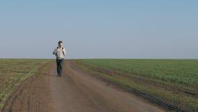 Turist- ung man som går in mot på en grusväg till och med ett grönt fält stock video