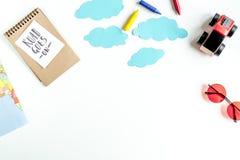 Turist- utrustning med leksaker och anteckningsboken för att resa med ungar på vit åtlöje för bästa sikt för bakgrund upp royaltyfria bilder