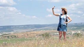 Turista activo de la mujer con la mochila que toma el selfie en el campo usando smartphone almacen de metraje de vídeo