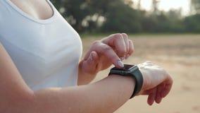 Turista activo de la mujer de la forma de vida que mira el reloj elegante del smartwatch de la tecnología Cierre macro del primer almacen de video