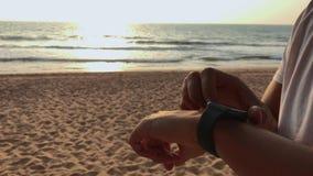 Turista activo del hombre de la forma de vida que mira el reloj elegante del smartwatch de la tecnología Cierre macro del primer  almacen de metraje de vídeo