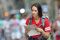 Turista adolescente de Frustated que lee un mapa fotografía de archivo libre de regalías