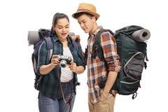 Turista adolescente femenino que muestra imágenes en una cámara a un varón a Imágenes de archivo libres de regalías