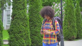 Turista africano del retrato a disposición desconcertado y perplejo de la mujer con un peinado afro con el teléfono almacen de metraje de vídeo