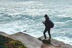 Turista alla moda della donna che per mezzo del telefono cellulare mentre stando su una roccia contro il mare blu con le onde fotografie stock libere da diritti