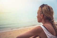 Turista allegro pensieroso della donna che si rilassa sulla spiaggia che esamina orizzonte durante il tramonto alla spiaggia trop fotografie stock libere da diritti