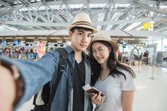 Turista asiático de los pares que toma un selfie en aeropuerto antes de viaje Foto de archivo