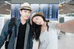 Turista asiático de los pares que toma un selfie en aeropuerto antes de viaje Fotografía de archivo