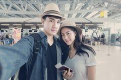 Turista asiático de los pares que toma un selfie en aeropuerto antes de viaje Fotos de archivo