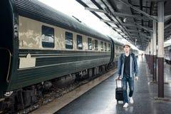 Turista asiático joven con el tren que espera del equipaje en la estación Imágenes de archivo libres de regalías