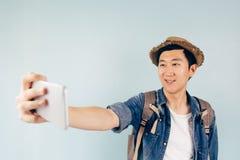 Turista asiático joven que sonríe y que toma un selfie aislado sobre fondo azul en colores pastel Fotografía de archivo libre de regalías
