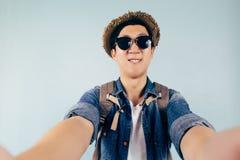 Turista asiático joven que sonríe y que toma un selfie aislado sobre fondo azul en colores pastel Imagen de archivo libre de regalías