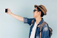Turista asiático joven que sonríe y que toma un selfie aislado sobre fondo azul en colores pastel Imagen de archivo
