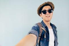 Turista asiático joven que sonríe y que toma un selfie aislado sobre fondo azul en colores pastel Foto de archivo libre de regalías
