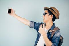 Turista asiático joven que sonríe y que toma un selfie aislado sobre fondo azul en colores pastel Imágenes de archivo libres de regalías