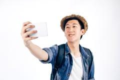 Turista asiático joven que sonríe y que toma un selfie aislado sobre wh Imágenes de archivo libres de regalías