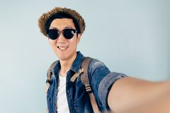Turista asiático joven que sonríe y que toma un selfie sobre fondo azul en colores pastel Fotografía de archivo