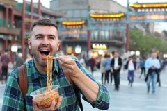 Turista in Asia che mangia le tagliatelle all'aperto immagine stock