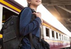 Turista asiatico della donna con lo zaino che sta alla stazione ferroviaria fotografia stock