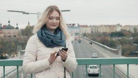 Turista atrativo vestido no vestuário desportivo usando a aplicação em Smartphone para navegar na cidade, posição da menina do mo Imagens de Stock Royalty Free