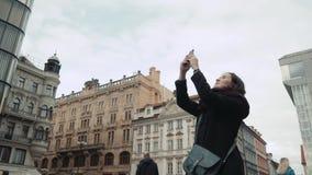 Turista bonito da jovem mulher em Praga, fazendo Selfie ou tomando a foto com seu telefone celular, conceito de viagem Fotografia de Stock Royalty Free