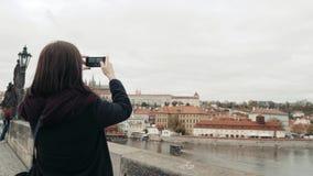 Turista bonito da jovem mulher em Praga, fazendo Selfie ou tomando a foto com seu telefone celular, conceito de viagem Imagens de Stock