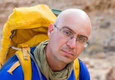 Turista calvo dell'alpinista di viaggiatore con zaino e sacco a pelo dell'uomo che esamina il ritratto della macchina fotografica Immagine Stock Libera da Diritti