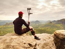 Turista cansado com a muleta da medicina e o pé quebrado fixados no imobilizador que descansa na cimeira da montanha imagem de stock