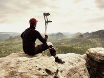 Turista cansado de dano com muletas da medicina O homem com pé quebrado na cinta de joelho caracteriza o descanso na cimeira roch foto de stock