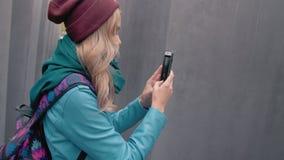 Turista caucásico de la muchacha de la cámara lenta con una mochila en el centro de Berlín en el otoño Entre las losas grises eno almacen de metraje de vídeo
