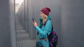 Turista caucásico de la muchacha de la cámara lenta con una mochila en el centro de Berlín en el otoño Hace una foto del monument almacen de metraje de vídeo