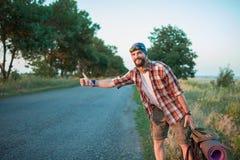 Turista caucásico del smilimg joven que hace autostop adelante Imágenes de archivo libres de regalías
