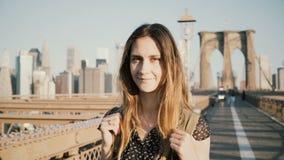 Turista caucásico femenino positivo joven con la mochila que mira la cámara, sonriendo en el puente de Brooklyn soleado, Nueva Yo almacen de metraje de vídeo