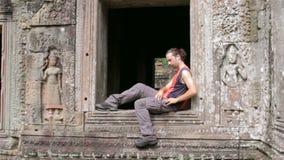 turista caucásico que usa el teléfono móvil en angkor almacen de video