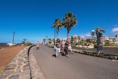 Turista che cammina in linea costiera di Las Americhe il 23 febbraio 2016 a Adeje, Tenerife, Spagna Fotografia Stock