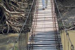 Turista che cammina su un ponte di legno della sospensione Fotografia Stock