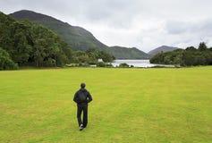 Turista che cammina sul prato inglese al lago Muckross Immagine Stock