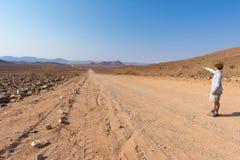 Turista che cammina sull'incrocio di strada 4x4 il deserto variopinto a Twyfelfontein, nel Damaraland maestoso Brandberg, DES sce Immagini Stock