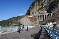 Turista che cammina sulla strada alla diga di Kurobe Fotografie Stock Libere da Diritti