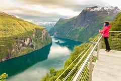Turista che esamina Geirangerfjord dal punto di vista Norvegia di Flydasjuvet Fotografia Stock