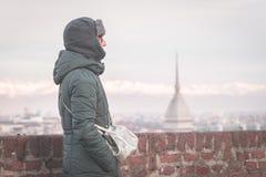 Turista che esamina vista panoramica di Torino Torino, Italia dal balcone qui sopra Orario invernale, alpi snowcapped nei precede Fotografie Stock