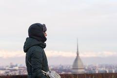 Turista che esamina vista panoramica di Torino Torino, Italia dal balcone qui sopra Orario invernale, alpi snowcapped nei precede Fotografie Stock Libere da Diritti