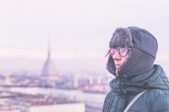 Turista che esamina vista panoramica di Torino Torino, Italia dal balcone qui sopra Orario invernale, alpi snowcapped nei precede Immagine Stock