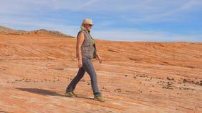 Turista che fa un'escursione nella donna del deserto che cammina sulla roccia rossa del parco Fotografia Stock