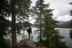 Turista che fa un'escursione sul lago alpino con il cane fotografia stock